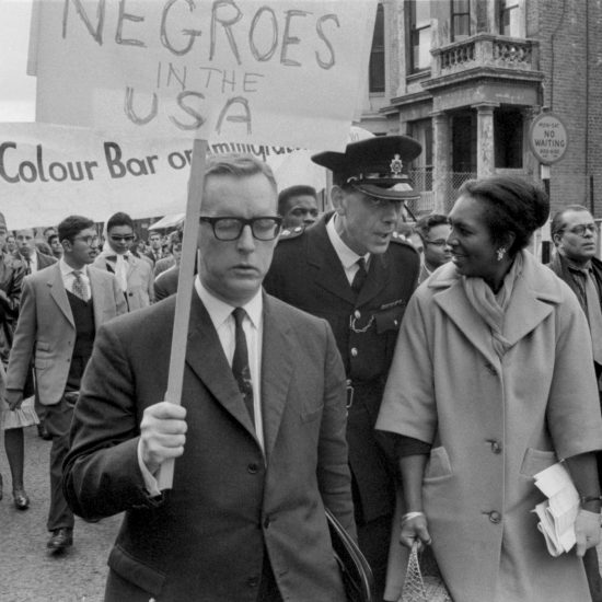 A police officer chats with a demonstrator during a civil rights march in Notting Hill, West London, circa 1963