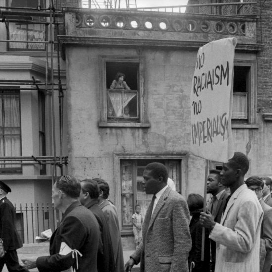 Bystanders watch as a civil rights demonstration passes through Notting Hill, West London, circa 1963