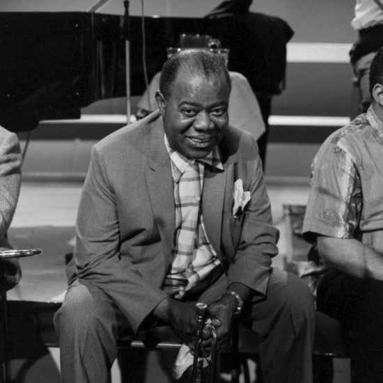 Louis Armstrong sits onstage and smiles at the camera during a rehearsal break at BBC-TV Theatre, Shepherd's Bush, London, on 03 June 1965
