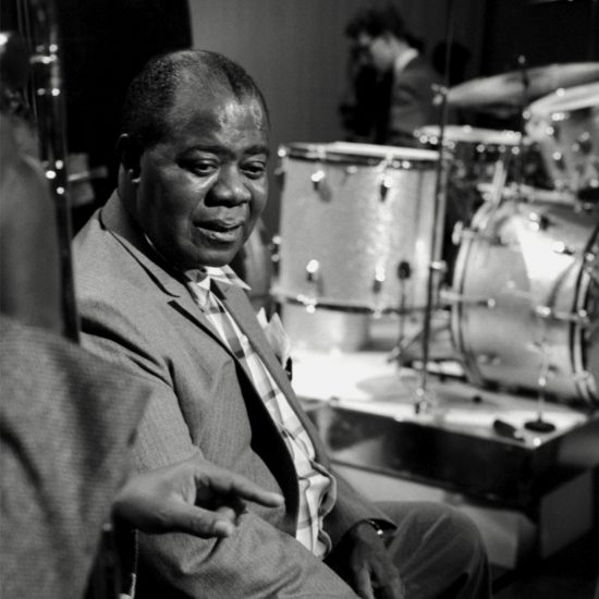 Louis Armstrong holds a cigarette and listens to a band member during a rehearsal break at BBC-TV Theatre, Shepherd's Bush, London, on 03 June 1963