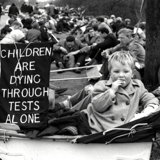 During a roadside break, a toddler in a pram is accompanied by the banner 'Children Are Dying Through Tests Alone' on the 1962 Aldermaston to London March against nuclear research. The toddler is eating a biscuit, and several of the resting marchers in the background of the frame are also eating