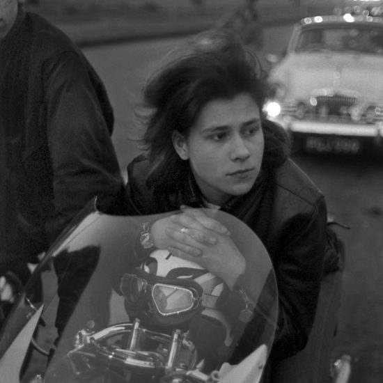 A female motorbike rider/Rocker sits on her bike and rests her hands on her helmet, whilst taking a break on the hard shoulder of the North Circular at dusk, on her way to the Ace CafŽ, circa 1964