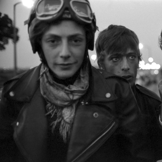 Three male motorbike riders/Rockers in mid-shot, whilst taking a break on the hard shoulder of the North Circular at dusk, on their way to the Ace CafŽ, circa 1964