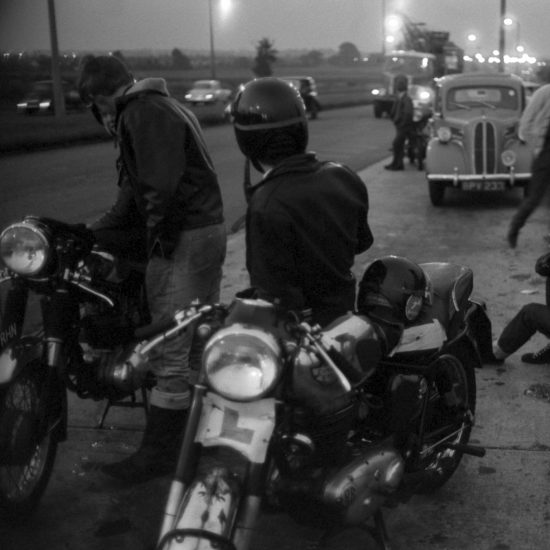 Several motorbike riders/Rockers take a break on the hard shoulder of the North Circular at dusk, on their way to the Ace CafŽ, circa 1964