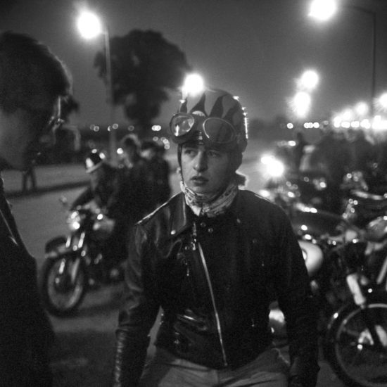 A motorbike rider sits on his bike at the side of the road and chats with a friend, during a meet-up of bikers on the way to the Ace Café, circa 1964