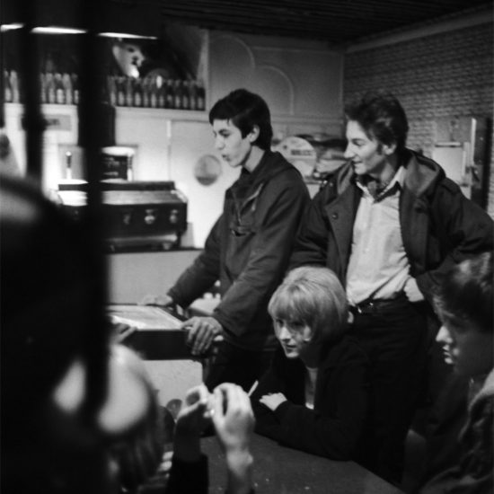 Male and female motorcyclists play the pinball machine and chat in a coffee bar, England 1964