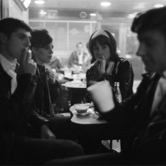 Fashionably dressed young women and male bikers smoke and chat in a café, England 1964
