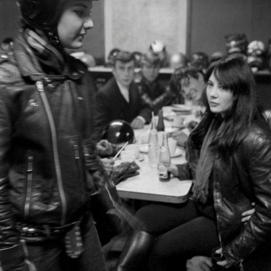 Female motorbike rider in crash helmet walks past female rocker seated at table, Ace Cafe, circa 1963/4