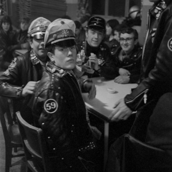 Members of the 59 Club sit around a cafe table in Paddington and socialise, including a biker wearing a Nazi cap who stares at the camera, circa 1963/64