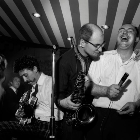 Blues Inc. gigging at the Marquee, shot in medium shot from below the stage. L-R: Alexis Korner on guitar, Dick Heckstall-Smith on saxophone and Cyril Davies on harmonica share a joke, Ginger Baker on drums and Art Themen on saxophone, circa 1962