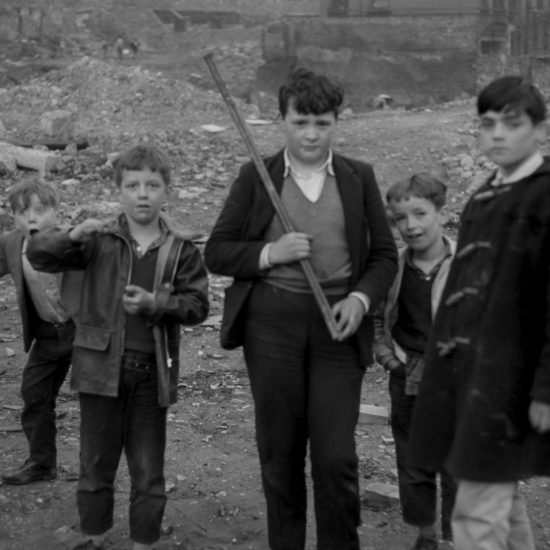 Five boys play in the rubble of a West London post-war bomb site, circa 1961. One boy holds a stick and looks to camera