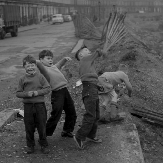 Four small boys laugh as they throw rocks across a post-war West London bomb site, circa 1961. An entire side of a street has been demolished, leaving a large play area
