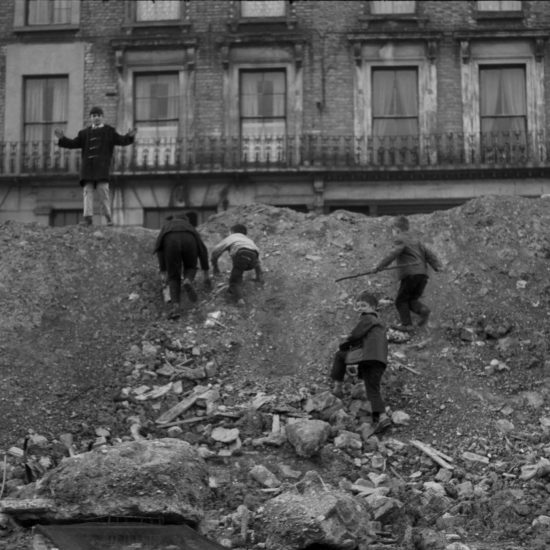 Five small boys clamber up the sides of a West London Second World War  bomb crater, circa 1961. A row of terraced houses can be seen in the background, probably in Notting Hill