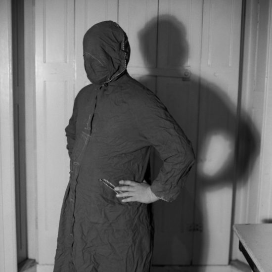 A male sex worker wearing a home-made gimp suit fashioned from a coat stands with his hands on his hips and his face obscured, West London, circa 1964