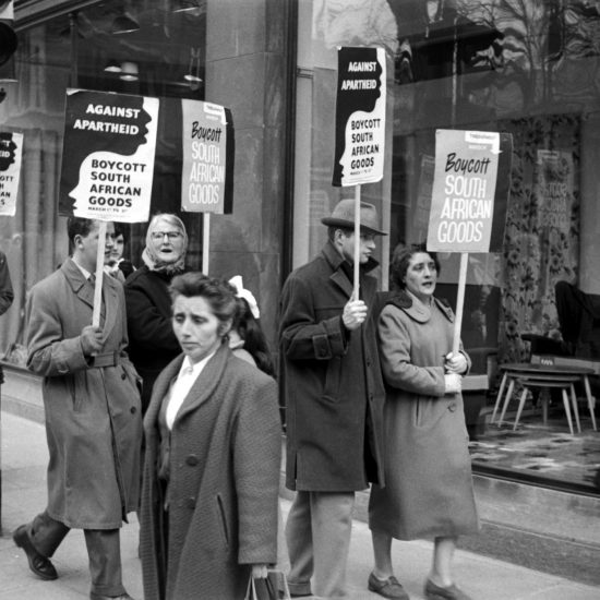 During a 1960 march against apartheid, protestors hold banners that state 'Against Apartheid - Boycott South African Goods March 1st-11th'. The protestors are marching down a central London street and are outside a furniture store