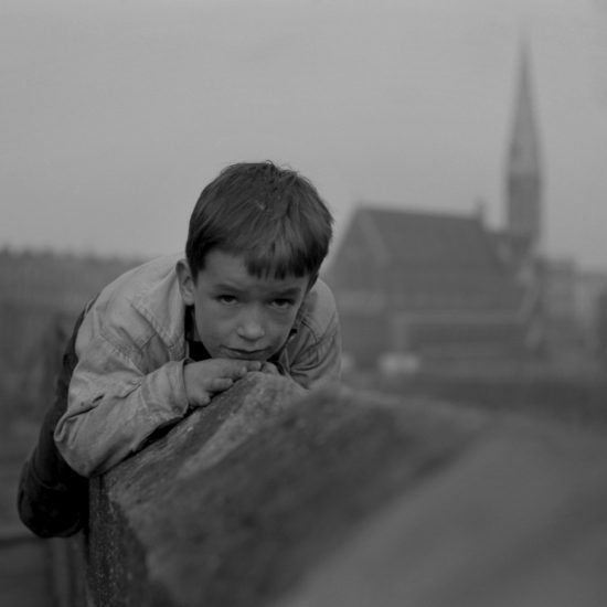 A small boy lies on top of a wall and stares at the camera in West London, circa 1961. A row of terraced houses and a church can be seen in the background