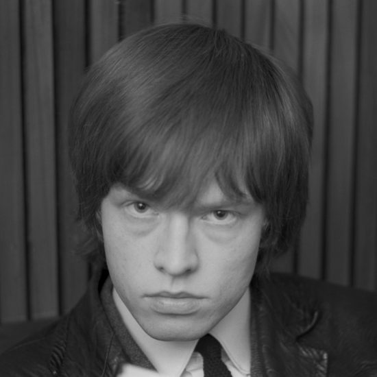 In 1964, Brian Jones of the Rolling Stones looks straight at the camera with a belligerent stare, in close-up