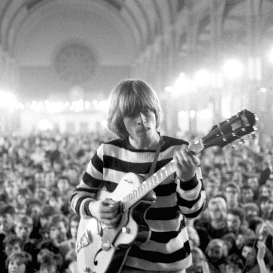 Brian Jones plays guitar with his back to the audience during the Rolling Stones set at the All Night Rave at Alexandra Palace, London, on 24 June 1964. Shot from the stage with the audience in the background