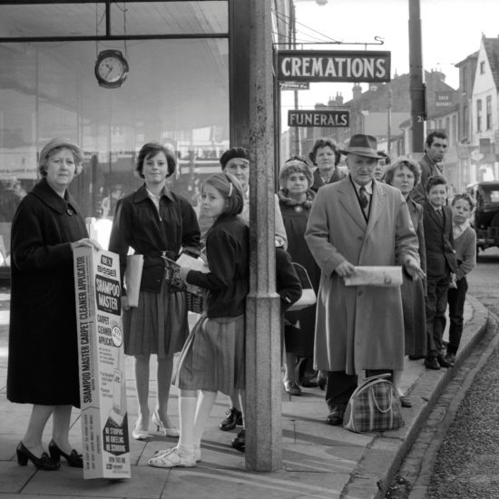 Shoppers in Kingston, west London queue at a bus stop in front of a funeral parlour, circa 1961