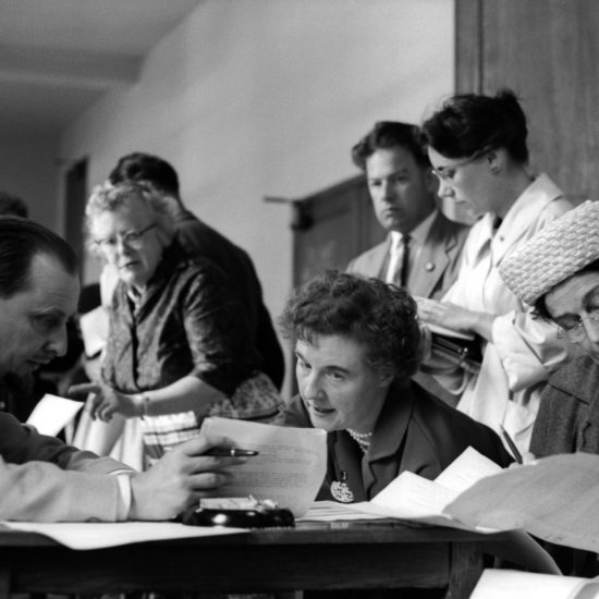 CND London committee members look at paperwork, with founder and Organising Secretary Peggy Duff in the background, circa 1962