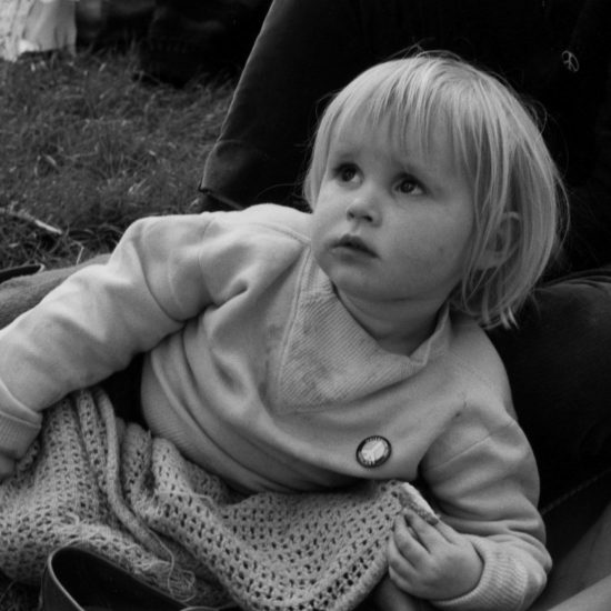 A small blonde girl lies on the ground and eats a biiscuit whilst wrapped in a blanket during a rest stop on the Aldermaston to London March of 1962. She is wearing a CND badge and is lying across an adult's legs