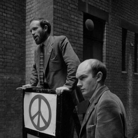 During a small Campaign for Nuclear Disarmament demonstration outside the London School of Economics, two men address an off-screen crowd. One stands on a small lectern with a CND logo tacked to the front, the other man stands next to the lectern, circa 1963