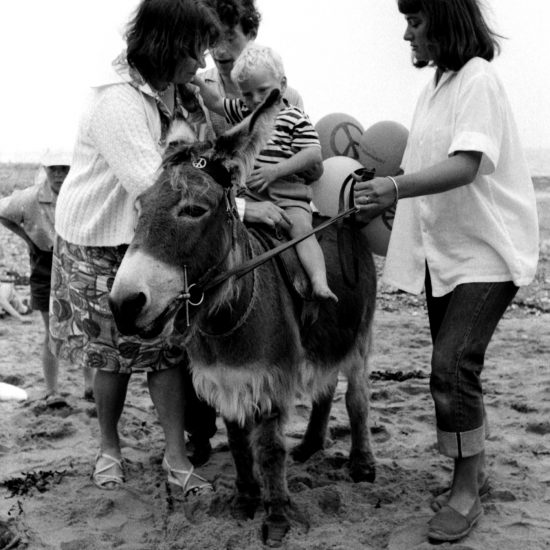 A small boy is placed on the back of a donkey on the beach, by three adults. The donkey has a CND sign on its bridle, balloons with the CND logo are tied to its tail, and another small boy is just visible in the background, circa 1963