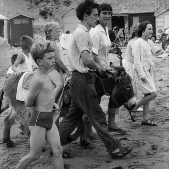 During a CND outing to the beach, a man and a woman lead a donkey across the sand, in front of a cliff and some beach huts with holidaymakers. There is a blonde girl with plaits on the donkey, and several girls and boys walking alongside, circa 1963
