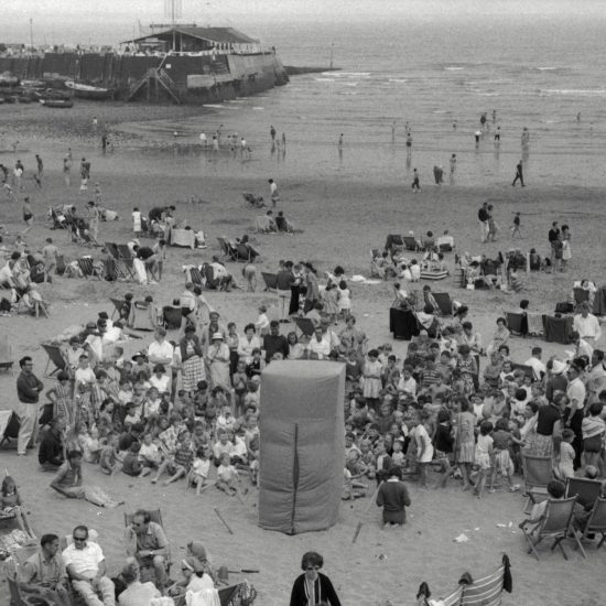 During a CND outing to the beach, children and adults gather around a Punch and Judy tent on the sand. A small harbour is visible in the background of the shot, with boats and a building on the harbour wall, and holidaymakers sit on deckchairs in the foreground of the image, circa 1963