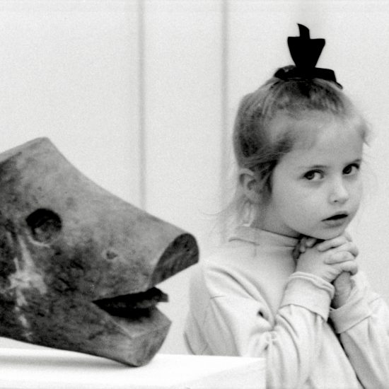 A young girl looks at the camera next to a carved wooden head during the Alexander Calder mobiles/stabiles exhibition at the Tate Gallery, London, July 1962