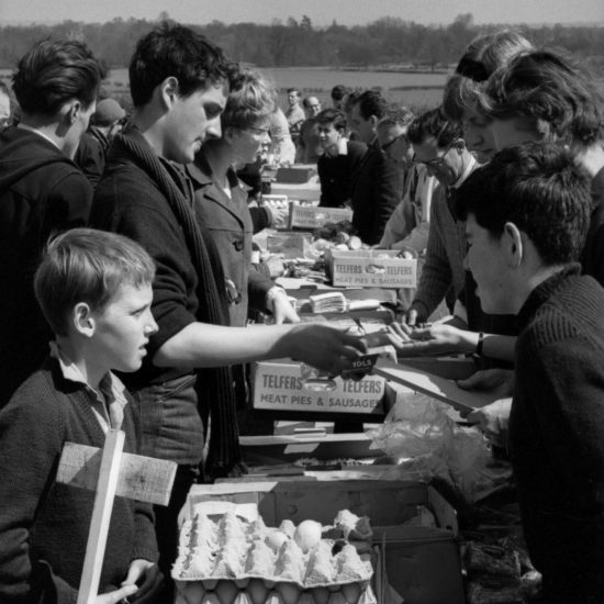 Peace movement activists hand out food during an overnight stop on the Aldermaston to London March of 1962. Trestle tables set up in a field have eggs, meat and other basic food items on them and are surrounded by peace marchers