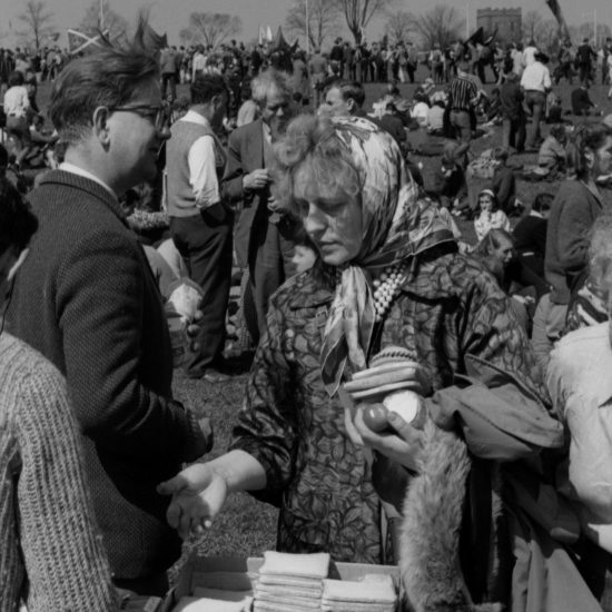 A woman in a headscarf gathers food items during an overnight stop in the grounds of Windsor Castle, on the Aldermaston to London March of 1962. Trestle tables set up in a field have eggs, meat, sandwiches and other basic food on them and are surrounded by peace activists distributing the food amongst the marchers