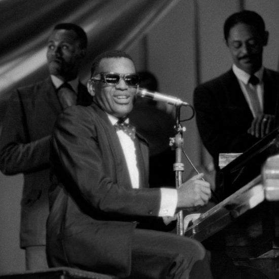 American musician Ray Charles sits at the piano on stage and faces the audience, with several band members in the background, circa 1963