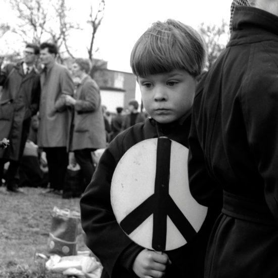 A blond male child holds a CND banner and looks wistful during the Aldermaston-London CND march, circa 1960. Aldermaston, Berkshire, was the site of an atomic arms research centre