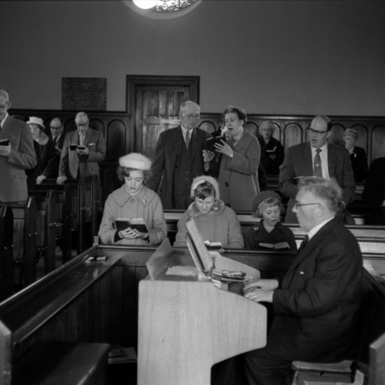A small congregation sing hymns in the parish church in Kinglassie mining village, Fife, Scotland; including three children and a church organist in the foreground, circa 1963