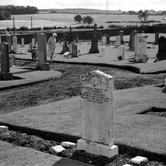 A woman and small girl look at a grave in the Kinglassie, central Fife mining village cemetery, surrounded by fields, circa 1963
