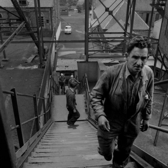 Miners ascend a staircase outside the coal face in the mining village of Kinglassie, Fife, Scotland: there is a miner in the forground and three of his colleagues further down the steps. The colliery buildings can be seen in the background, as well as fields and trees: image circa 1963