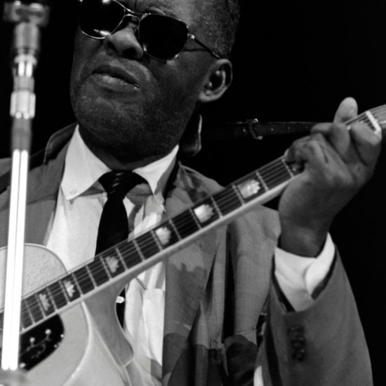American blues and gospel singer and guitarist The Reverend Gary Davis stands at the microphone on stage and plays guitar, in close up, during the 1964 Blues and Gospel Caravan tour of the UK