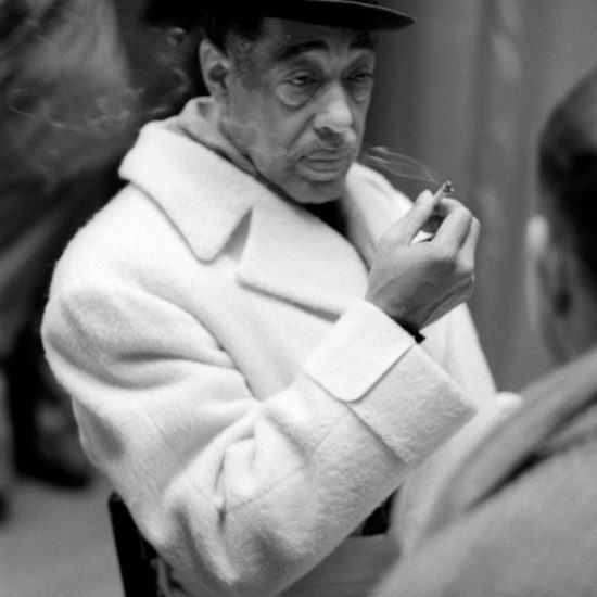 American composer, pianist, and bandleader Duke Ellington sits and smokes during band rehearsals in London, circa 1962