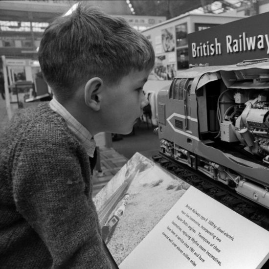 A small boy looks at an engineering display by British Railways during a science and engineering exhibition, London circa 1965