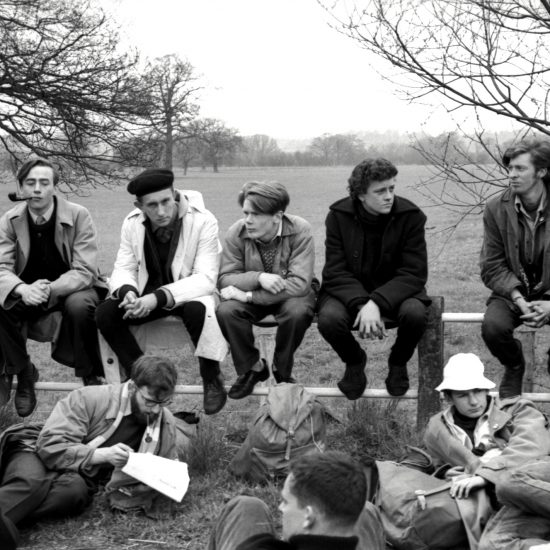 Five white men sit on a fence on the edge of a field during an overnight stop on the Aldermaston to London March of 1962. The men on the fence are surrounded by other men resting on the ground, and one male is smoking a pipe