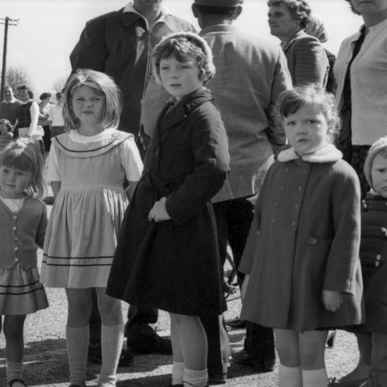 Four young girls and one male toddler stand in front of a group of adults and watch as the 1962 Aldermaston to London March passes through their village. In the background of the frame other villagers can be seen standing by the roadside, waiting for the marchers to pass