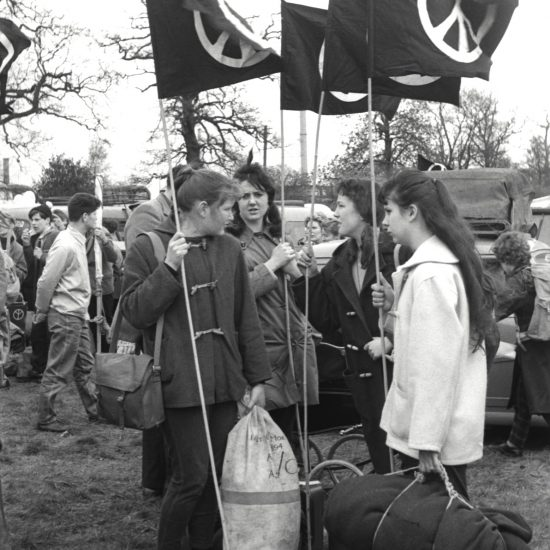 Four young women hold CND banners and duffel bags in a field, during the Aldermaston to London anti-nuclear protest march held in April 1960