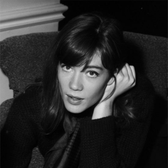 French singer-songwriter Françoise Hardy looks up at the camera with of a copy of a Bourjois advertisement in front of her, London, early 1964