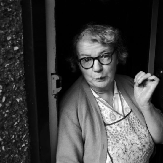 An elderly lady wearing glasses, a cardigan and an apron stands at her front door and purses her lips during an interview in Frimley and Camberley, Surrey, circa 1963
