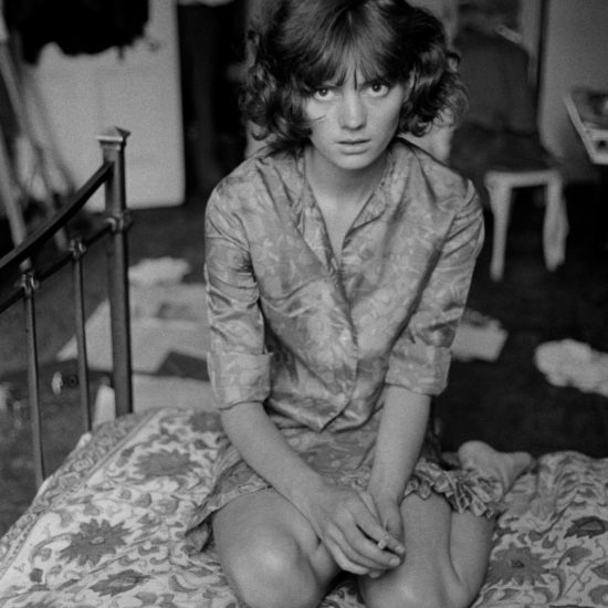 Gala Michell holds a cigarette and gazes at the viewer whilst sitting on a bed in a messy bedroom. A man stands in the doorway in the background of the scene