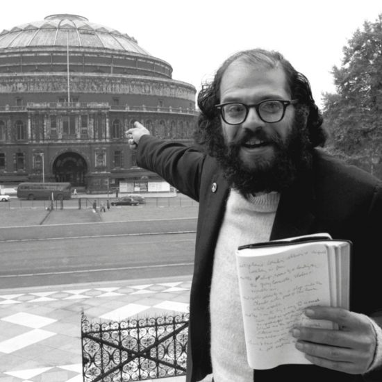 American beat poet and author Allen Ginsberg points to the Royal Albert Hall from the steps of the Albert Memorial. In his left hand he holds a notebook with writing in it: photograph taken during the planning of the International Poetry Congress in June 1965
