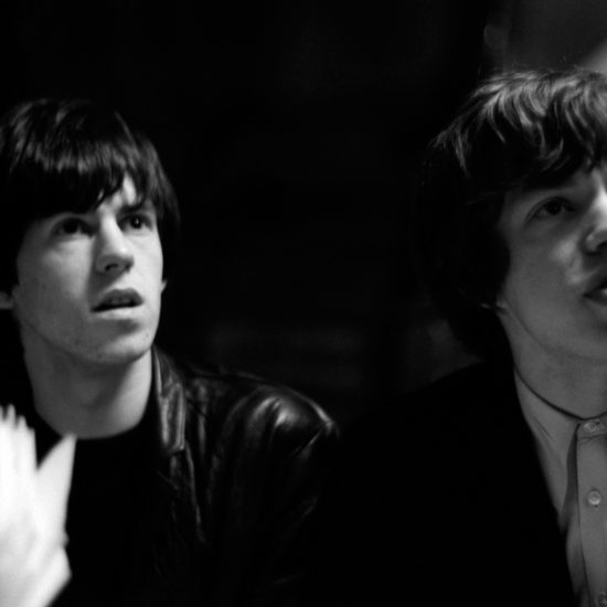 Keith Richards (left) and Mick Jagger (right) of the Rolling Stones sit together at a cafŽ table and look out of shot, in close up