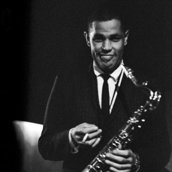 Dexter Gordon holds a cigarette in his right hand and a saxophone in his left whilst smiling and looking at the camera. Image taken on stage at Ronnie Scott's