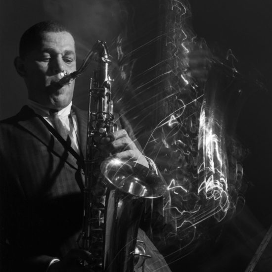 Dexter Gordon at Ronnie Scott's, Wardour Street, London, shot with flash and a long exposure to give light trails reflecting from Gordon's tenor saxophone, circa 1962